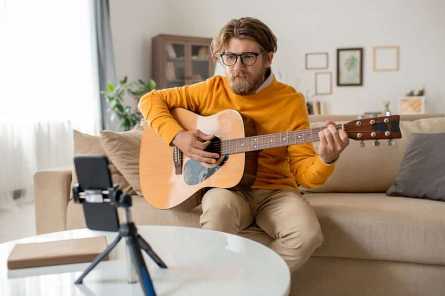 Young Musician Or Music Teacher Playing Guitar In Front Of Smartphone Camera